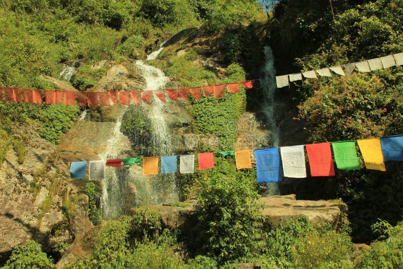 buddisten flags den små vattenfallet för den främre bönen arkivbild