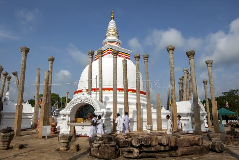 Buddisten vallfärdar ber på Thuparamaen Dagoba på Anuradhapura arkivbilder