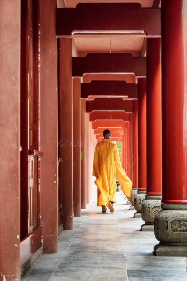 Buddistisk munk som promenerar den röda träkorridoren av en kloster royaltyfria bilder