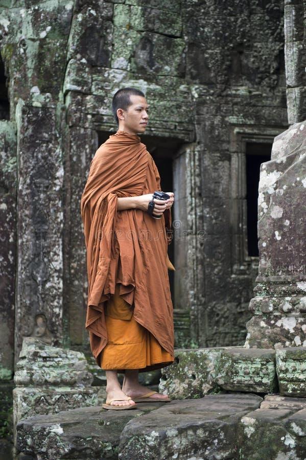 Buddistisk munk Stands på den gamla templet av Angkor Cambodja royaltyfria bilder