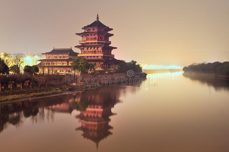 Buddistisk tempel med pagoden bredvid en tyst flod under skymning, Nanjing, Kina royaltyfri foto