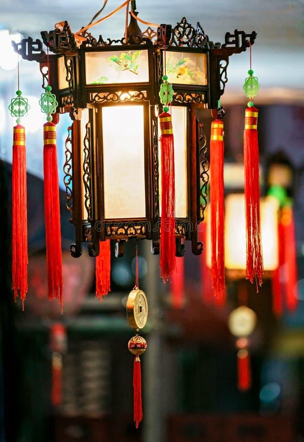Buddistiska dekorativa lyktor med röda tofsar som utomhus hänger på natten som gatabelysning för kinesisk feriecelebratio för nyt arkivfoto