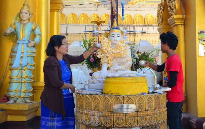 Buddistiska fantaster som badar Buddhastatyer på den Shwedagon pagoden royaltyfria bilder
