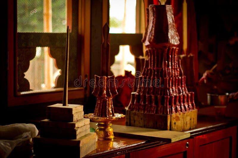 Buddistiska munkar av Bhutan gör stearinljus i deras Bhutan tempel I arkivbild