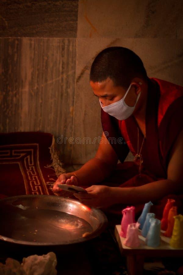 Buddistiska munkar av Bhutan gör stearinljus i deras Bhutan tempel I arkivfoto