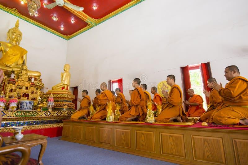 Buddistiska munkar ber på Buddhastatyn, den selektiva fokusen royaltyfri bild