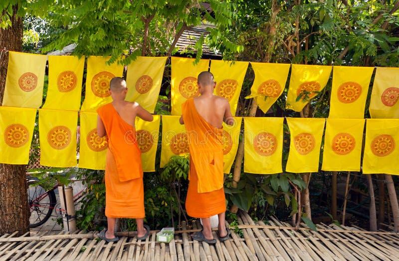 Buddistiska munkar dekorerade vid flaggor med religiösa symboler allt område utanför kloster arkivfoton