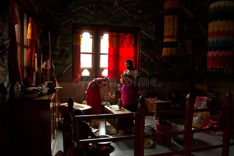 Buddistiska munkar från Bhutan gör stearinljus i deras Bhutan tempel I royaltyfri foto