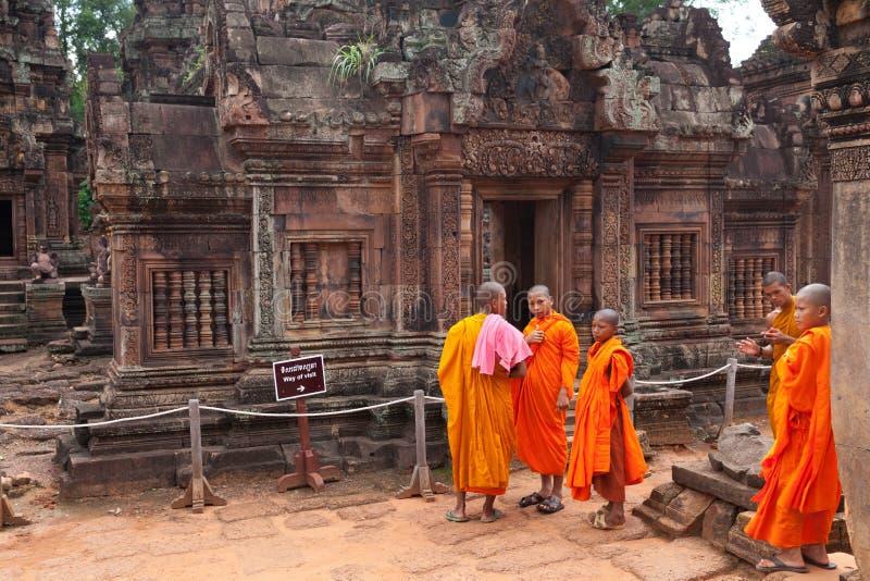 Buddistiska munkar observera den Banteay Srei templet, Cambodja royaltyfri bild