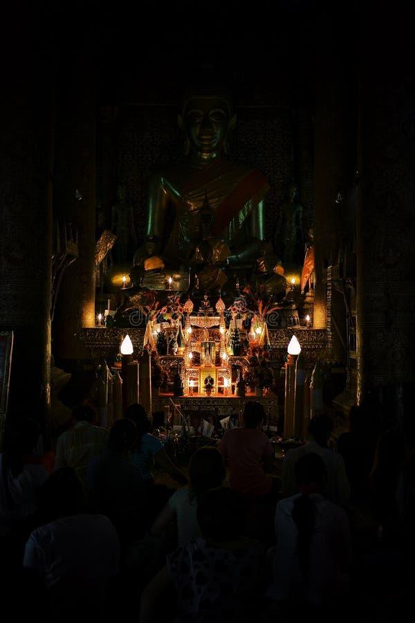 Buddistiska munkar som ber under en eftermiddagceremoni på deras wat arkivbild