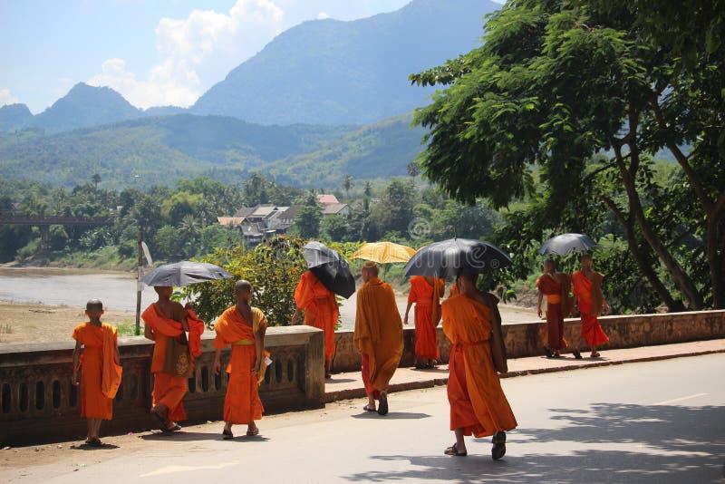 Buddistiska munkar som beskyddar under paraplyer längs den Nam khan floden - Laos royaltyfri bild