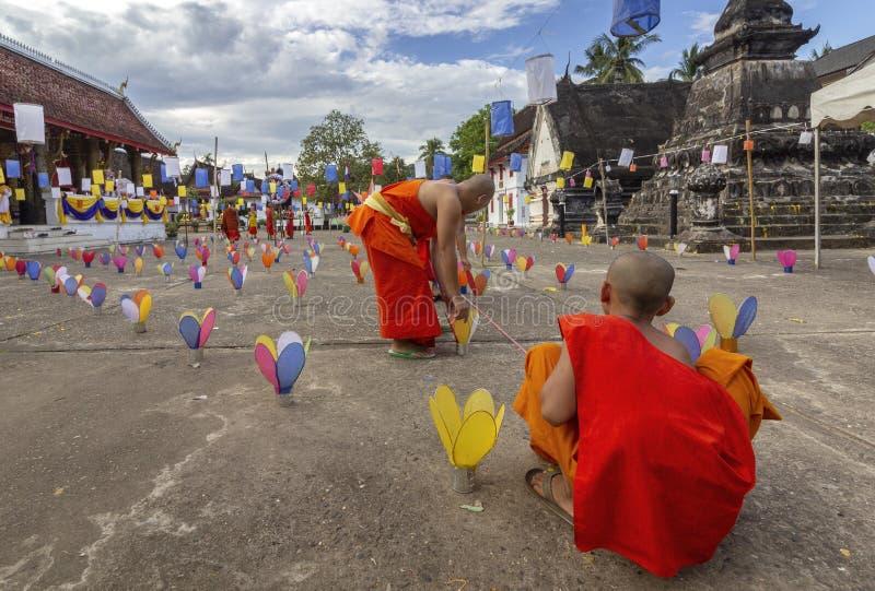 Buddistiska munkar som förbereder stearinljus för berömmen av Boun ok Phansa ferie, Laos fotografering för bildbyråer