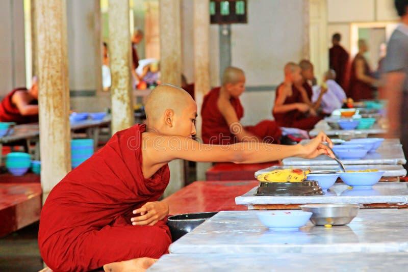 Buddistiska munkar som mottar donationer av mat, Mahagandayon kloster, Mandalay, Myanmar royaltyfria bilder