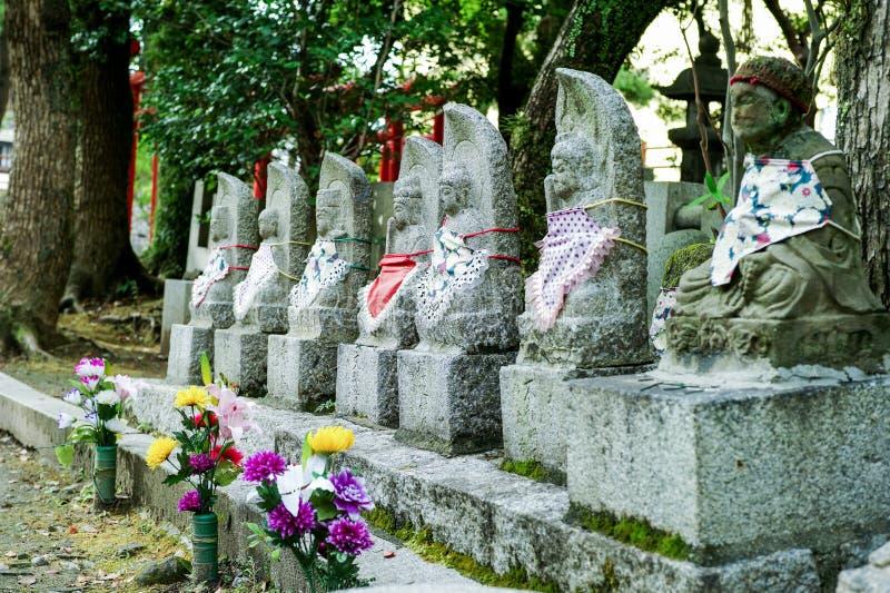 Buddistiska skulpturer för selektiv fokus på templet och relikskrin med blommor i vaser royaltyfri bild