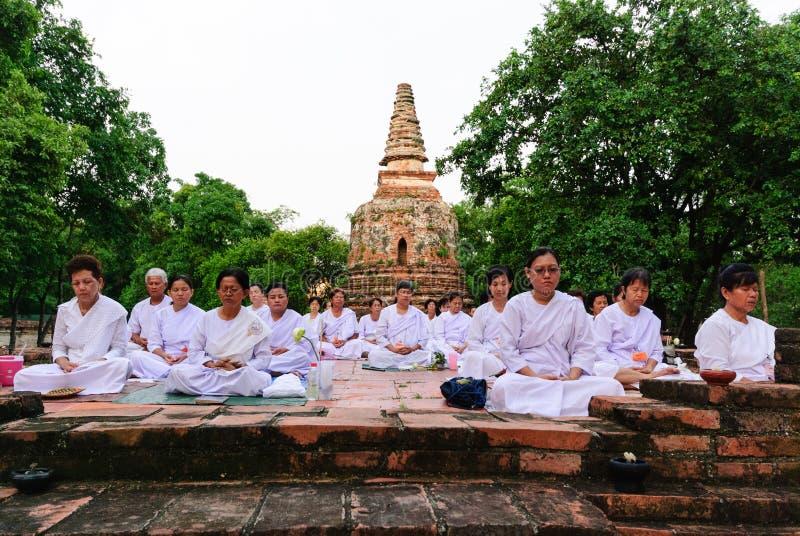 Buddistiskt folk som mediterar mot forntida arkivfoto