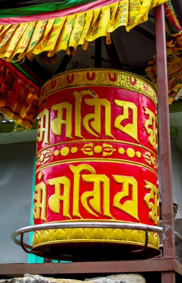 Buddistiskt rött bönhjul för Nepali med bokstavssymboler fotografering för bildbyråer