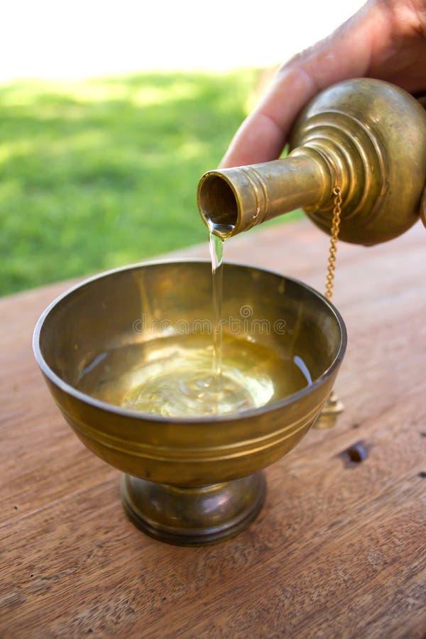 Buddists hällande vatten för gral arkivfoto