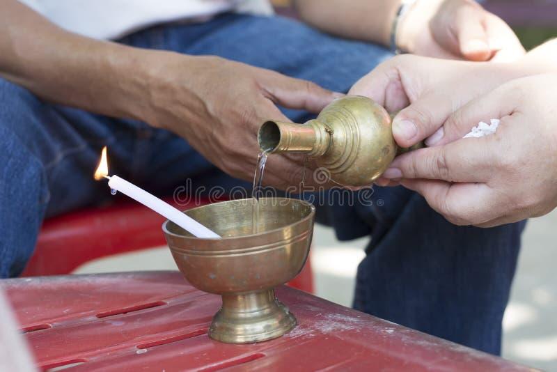 Buddists vatten för gral för ibation för man- och kvinnahand hällande fotografering för bildbyråer