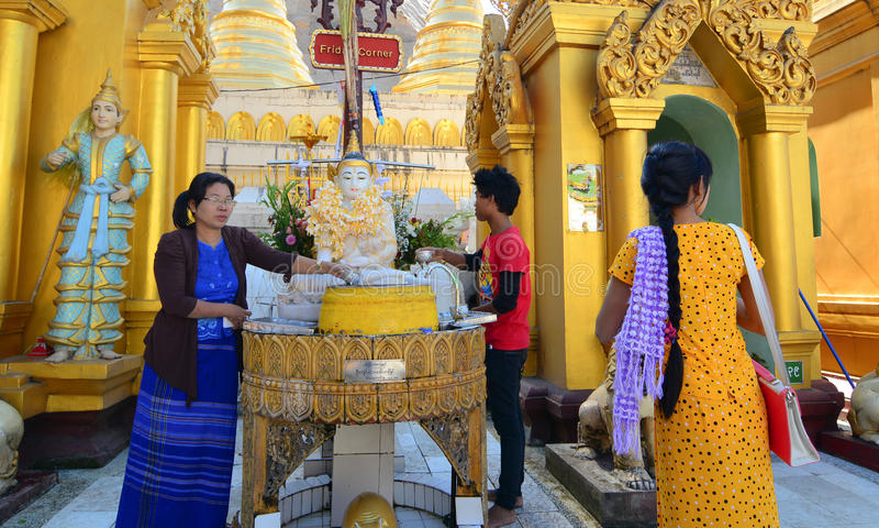 Buddyjskie dewotki kąpać się Buddha statuy przy Shwedagon pagodą obrazy stock