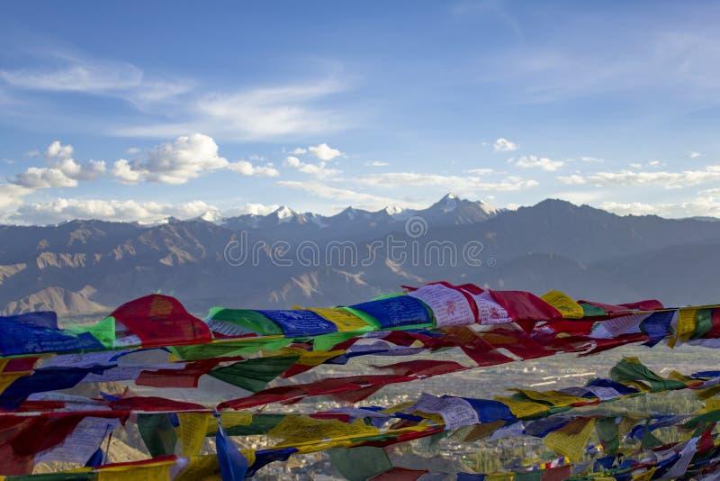Buddyjskie Tybetańskie stubarwne modlitewne flagi zamknięte w górę wiatru na zamazanym w zdjęcia royalty free