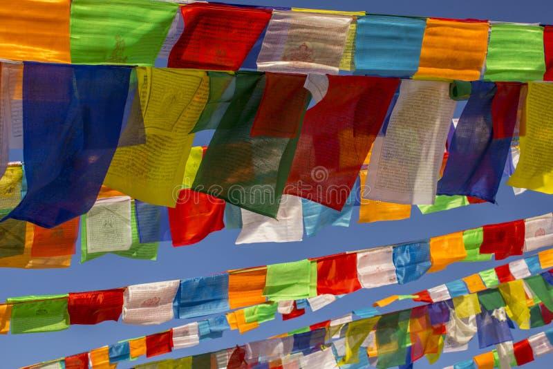Buddyjskie Tybetańskie stubarwne modlitewne flagi zamykają w górę czystego niebieskiego nieba przeciw fotografia stock