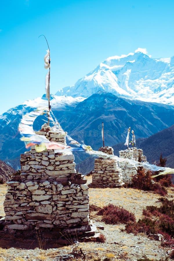 Buddysta rockowa stupa z modlitwą zaznacza dmuchanie w wiatrze w Manang okręgu Annapurna pasmo górskie, himalaje, Nepal zdjęcia stock
