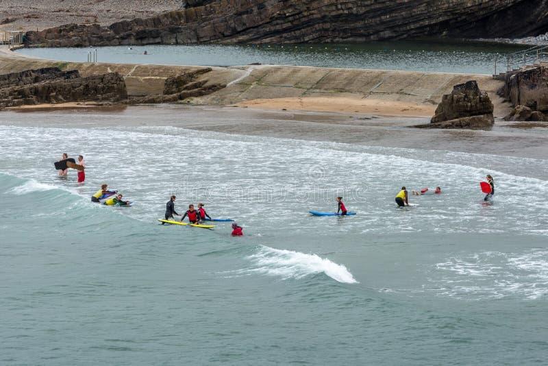 BUDE, CORNWALL/UK - 15-ОЕ АВГУСТА: Люди уча заниматься серфингом на Bude стоковые фотографии rf