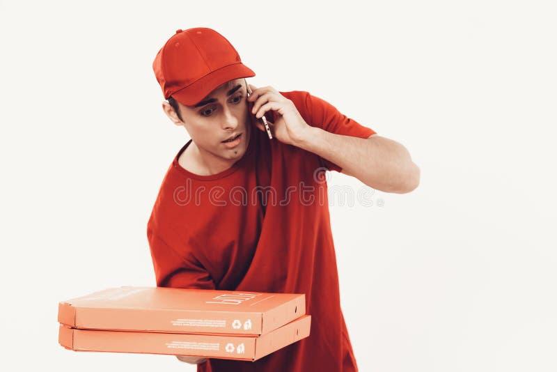 Budet i orange likformig talar in i telefonen arkivfoto