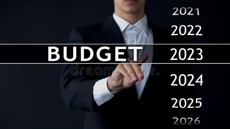 2023 budget, businessman selects file on virtual screen, annual financial report royalty free stock photography