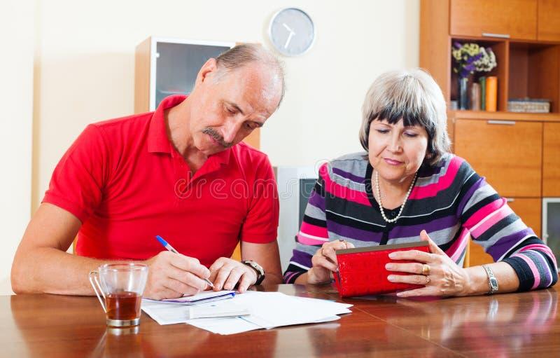 Budget calculateur de couples supérieurs tristes photographie stock