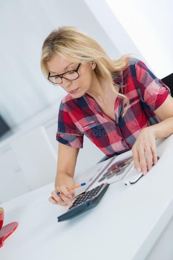 Budget calculateur de femme indépendante dans le bureau au bureau photo stock
