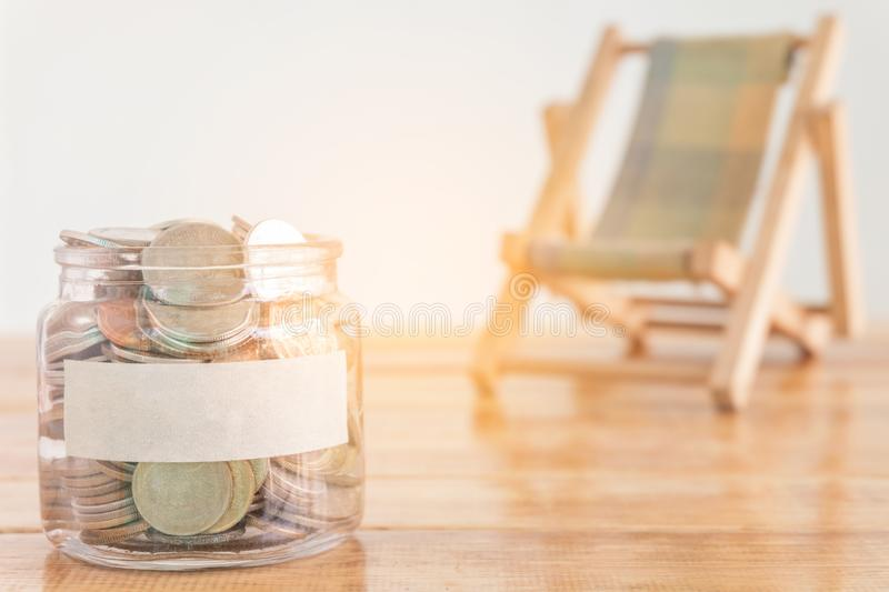 Budget concept, money savings concept. Collecting money in the money jar for your concept. Money jar with coins and beach seat on. royalty free stock images