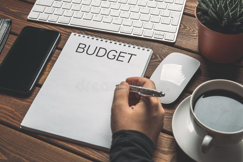 Budget concept. Woman planning finance on notepad with inscription Budget on wooden work place table with coffee, keyboard. Cellphone. Write idea success stock images