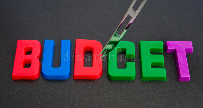 Budget cuts. A macro image of the word budget with a knife hovering over the word spelled out in large colorful upper case letters. A concept image covering royalty free stock photos