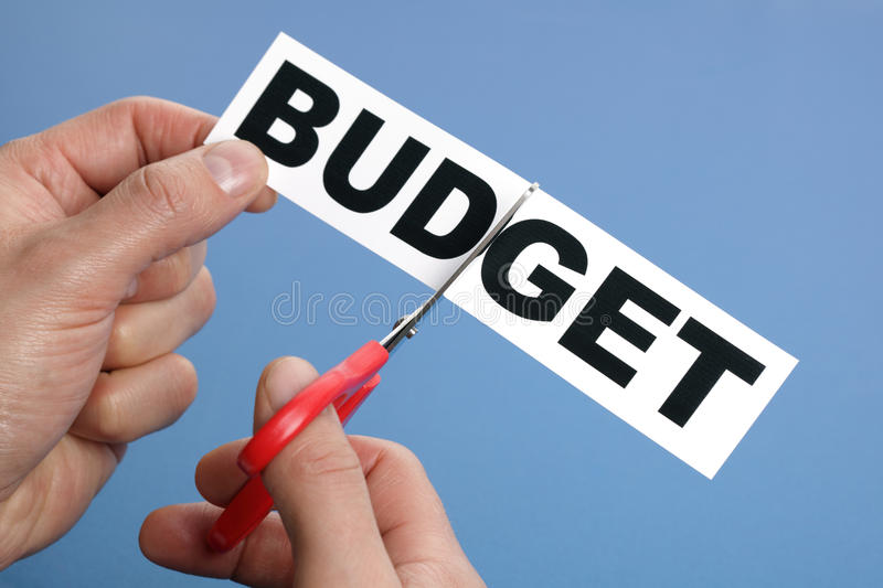 Budget cuts. Scissors cutting the word budget concept for recession or credit crisis stock photo