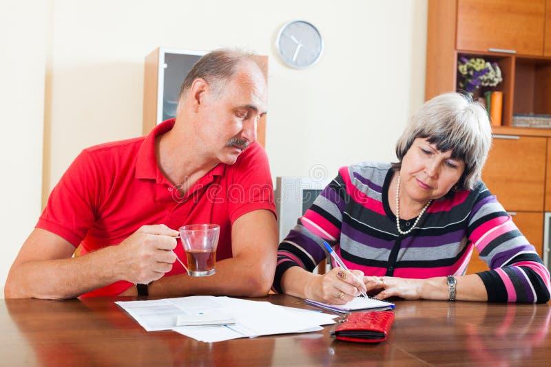 Budget de famille calculateur de couples supérieurs sérieux photographie stock