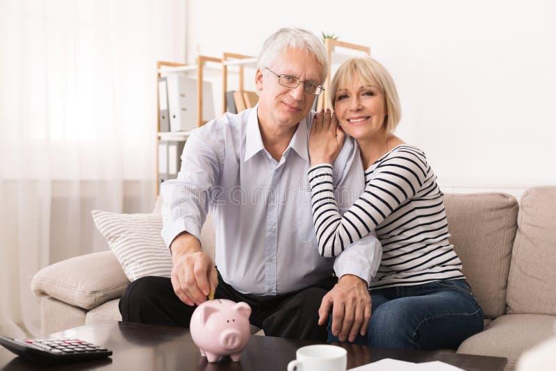 Budget de famille Couples supérieurs mettant la pièce de monnaie dans la tirelire image libre de droits