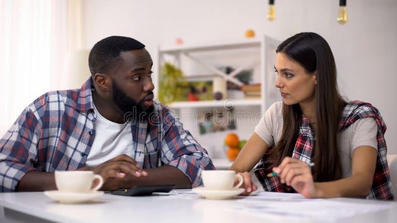 Budget de famille de planification d'homme de couleur et de jeune dame, comptant des revenus et des dépenses photos stock