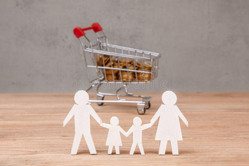 Budget of the family. Shopping cart full of coins and family symbol stock photography