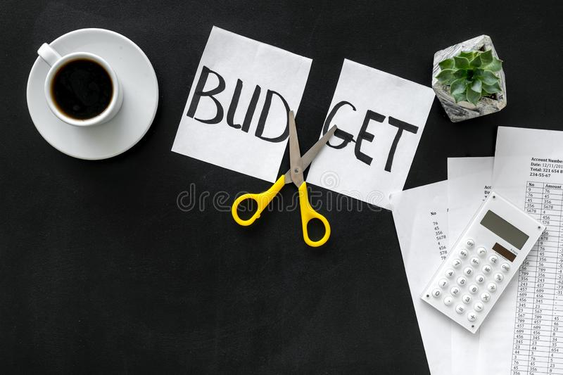 Budget reduce concept with accounting, sciccors and paper with cut word budget on black background top view mock-up. Budget reduce concept with accounting stock photography