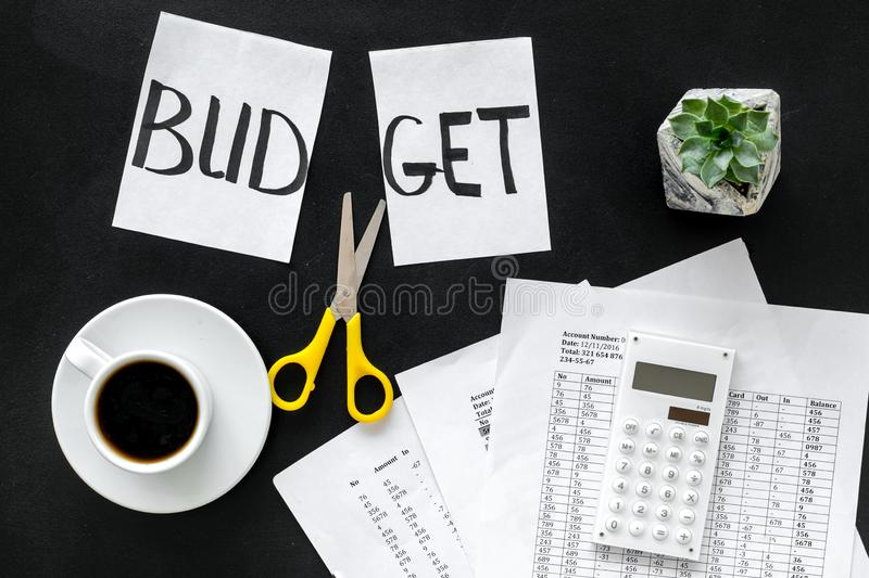 Budget reduce concept with accounting, sciccors and paper with cut word budget on black background top view. Budget reduce concept with accounting, sciccors and stock photo