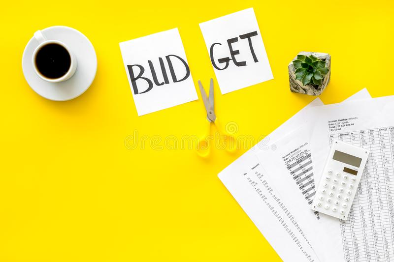 Budget reduce concept with accounting, sciccors and paper with cut word budget on yellow background top view mockup. Budget reduce concept with accounting stock photography