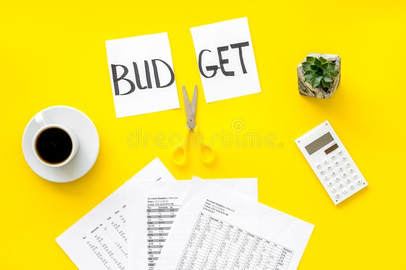 Budget reduce concept with accounting, sciccors and paper with cut word budget on yellow background top view. Budget reduce concept with accounting, sciccors and stock image