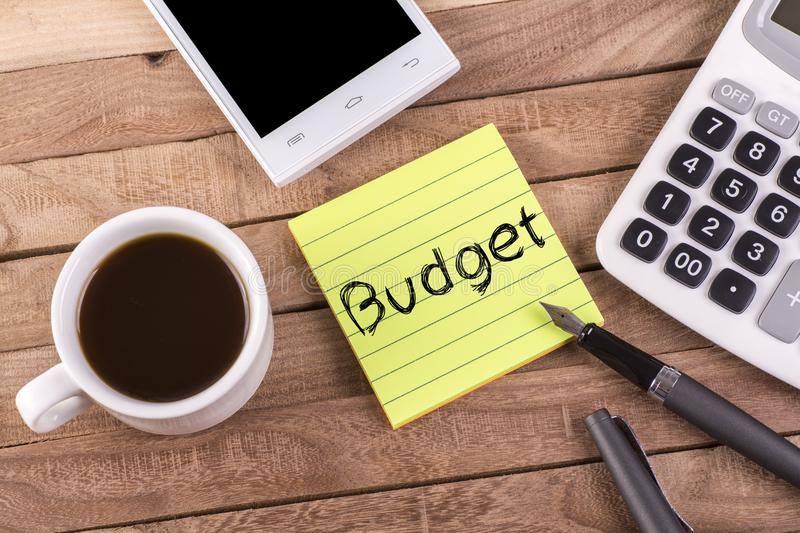Budget word on memo. With pen , coffee , mobile and calculator on wooden table stock photos
