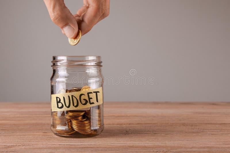 budgeter Den Glass kruset med mynt och en inskrift budgeterar Manhållmynt arkivbild