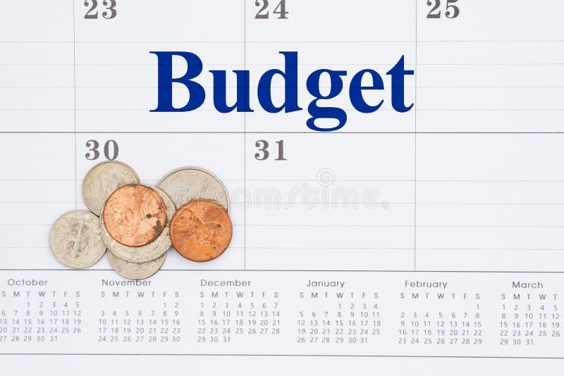 Budgetera ditt pengarmeddelande på en månatlig kalender med mynt fotografering för bildbyråer