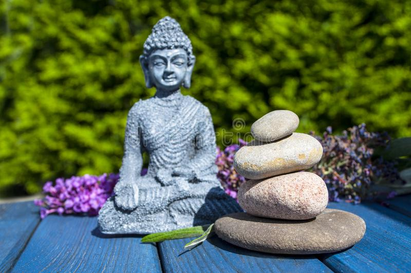 Budha figure with pyramide of stone of wooden background in the garden royalty free stock photo