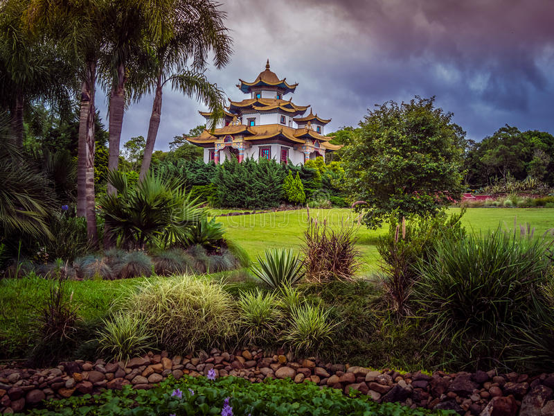Buddhist temple. In Gramado - Tres Coracoes - Brazil, the red and gold contrasts with the grey clouds in the sky royalty free stock photo