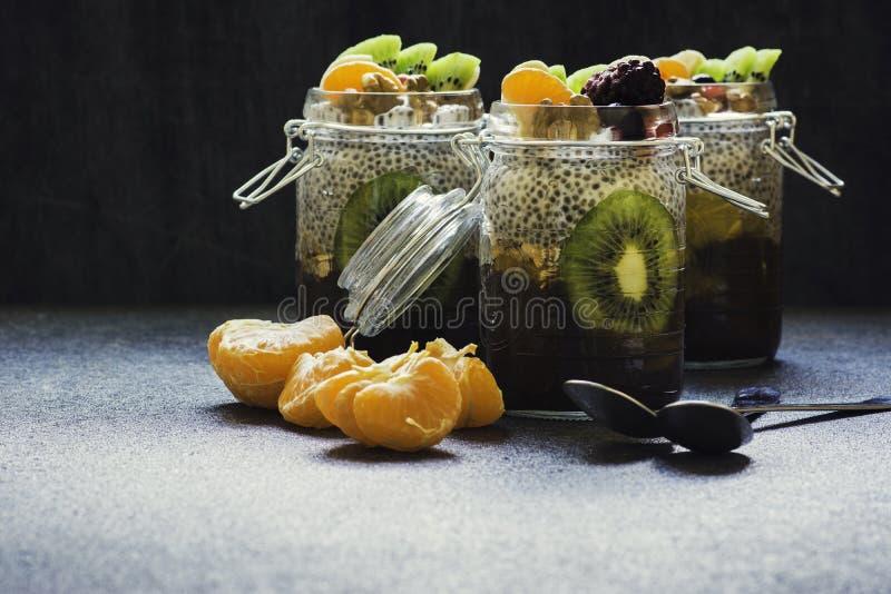 Budino fresco e sano di chia in un barattolo con i frutti ed in dadi sulla cima fotografia stock