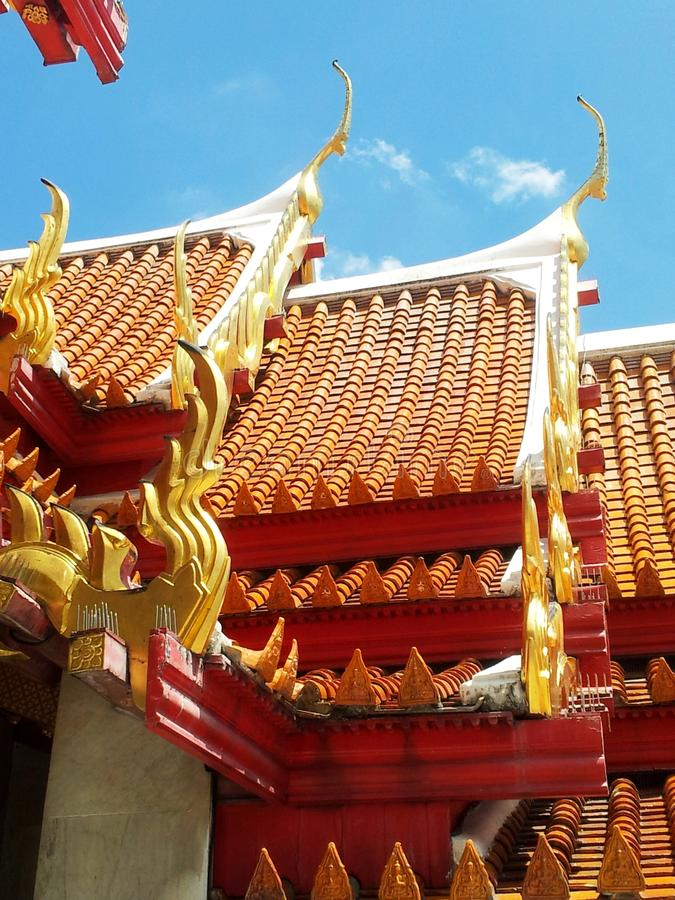Budist temple Bangkok. Roof Buddhist temple in Bangkok, the red and gold contrasts with the blue sky stock photography